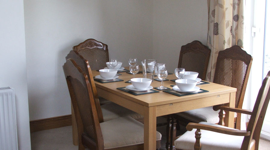 Dining table and chairs set for lunch with white crockery.