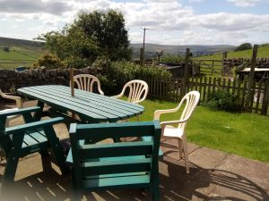 Shows the back garden with patio and views of the countryside.ack garden