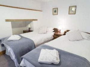 Shows the ground floor bedroom with beds made up as twin beds.