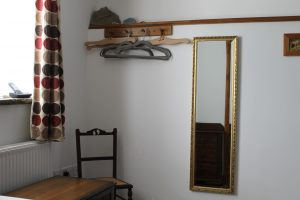 Shows hanging pegs, coat hangers, full length mirror and bedroom chair.