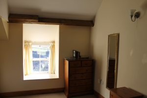 First floor front bedroom showing full length mirror and chest of drawers.
