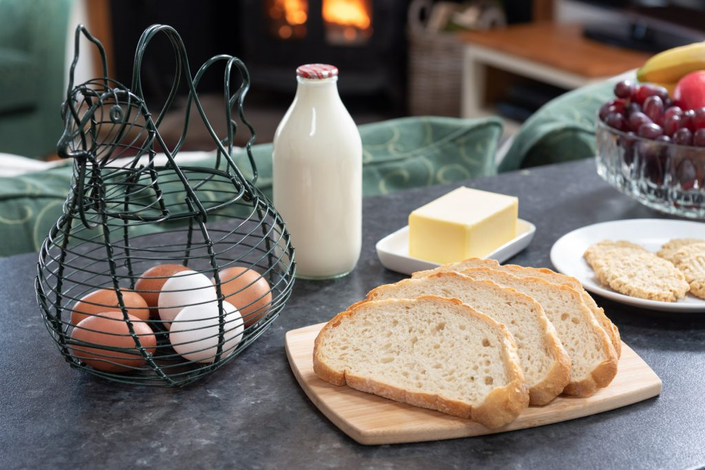 Eggs, bread, butter and a pint of milk in a glass bottle.