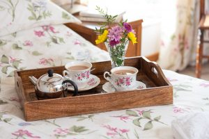 Breakfast tray on the bed in double room, showing cups of tea and flowers.