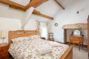 Double bedroom, showing oak bed, beams and fireplace (not working)