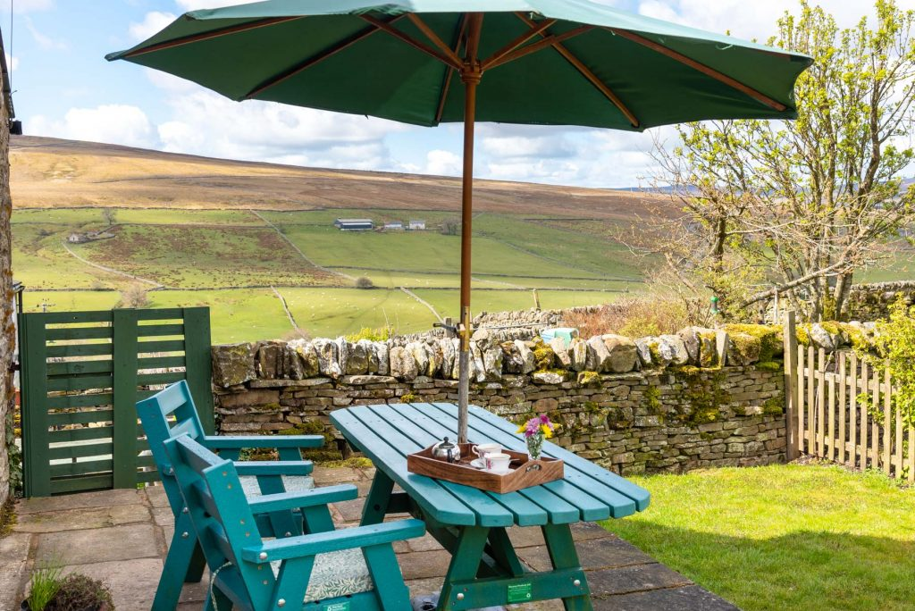 Patio table, chairs and parasol. Shows view of the countryside around Isaac's Byre.