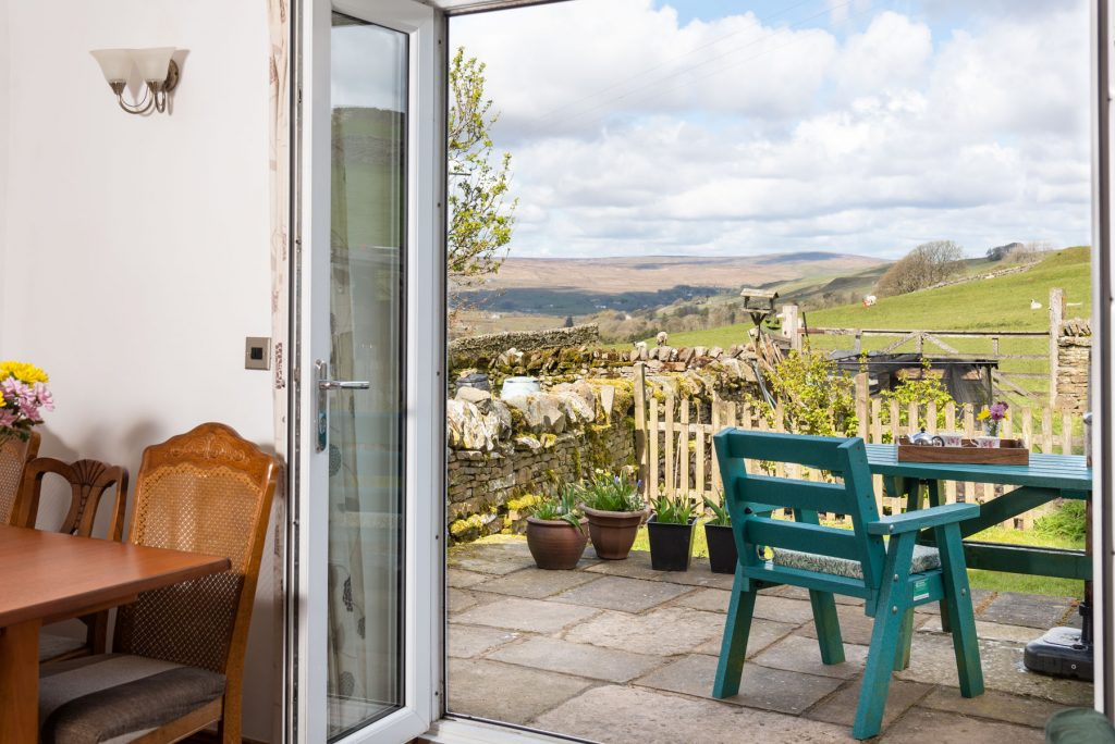 This shows the view through open patio doors, of patio with furniture, the grassed area and the distant view the North Pennines.