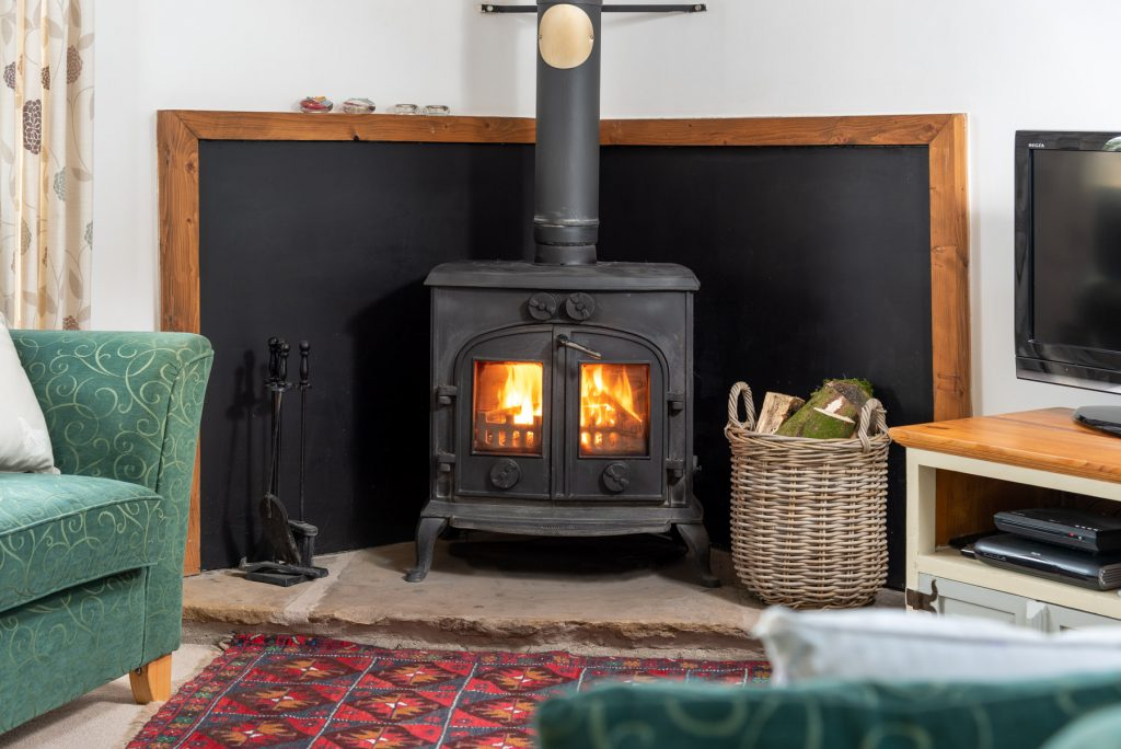 Shows the lit woodburning stove sitting on a stone fireplace with a log full basket